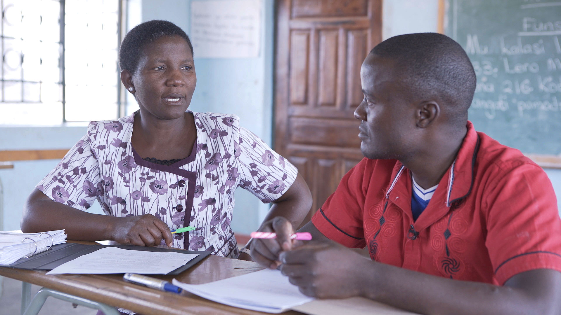 A mentor and teacher sit at a desk talking during a Catch Up mentoring and monitoring visit in Zambia.