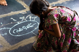 A child draws a mind map on the floor with chalk in a TaRL class in India.