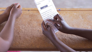 Picture of a desk, a child's hands on a page with a printed paragraph. A teacher's hands rest on the desk. During a Teaching at the Right Level literacy assessment in Zambia.