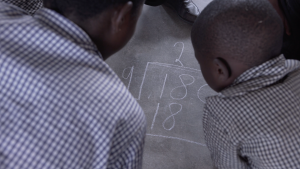 Children work on a long division sum in a TaRL classroom in Zambia.
