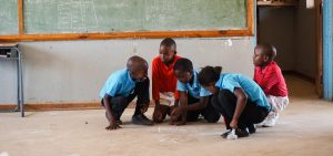 Children in a TaRL classroom in Botswana work together to complete a reading activity.