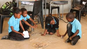 Children a TaRL classroom in Botswana use bundles, sticks, and chalk to solve a mathematics sum.