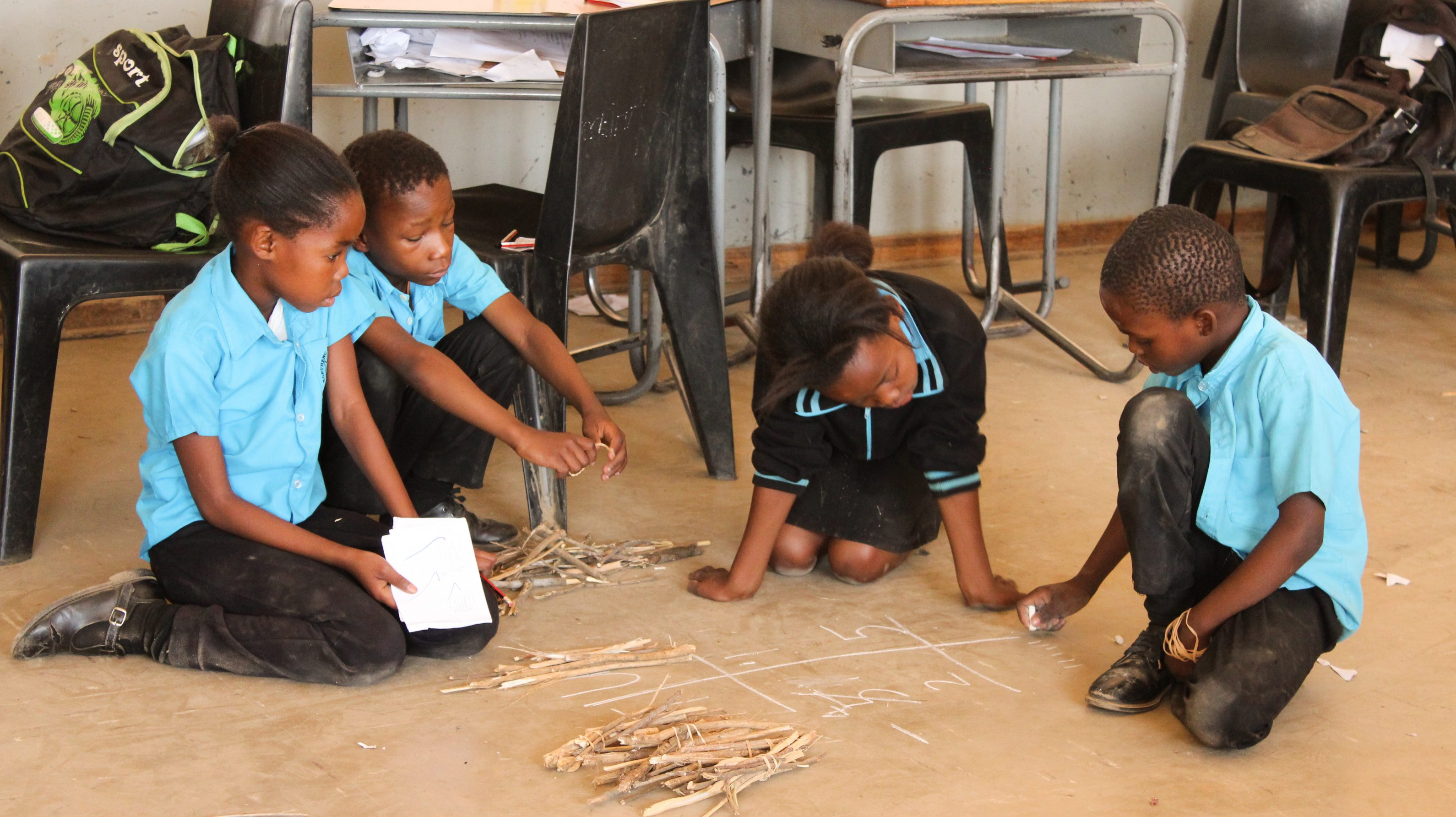 Three children watch as one child writes on the floor with chalk. Teaching at the Right Level materials (sticks tied in bundles) are on the floor next to them.