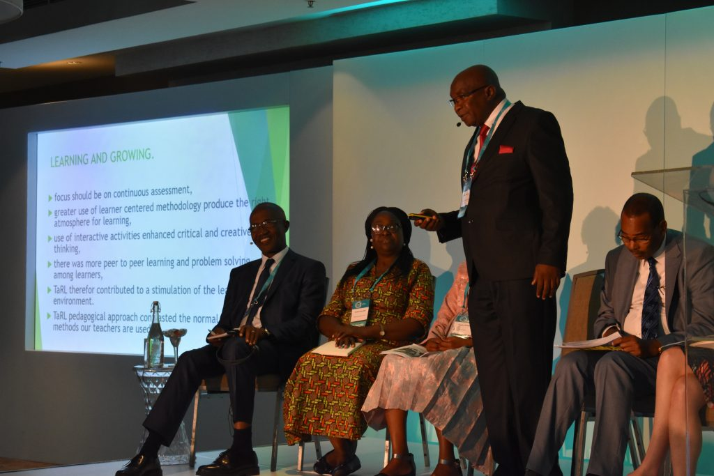 Mahuba Hazemba speaks on stage, while fellow panelists Raoul Kone, Cynthia Efua Bosumtwi-Sam, Angela Tsheole, and Habbat Abdi listen at the Teaching at the Right Level Conference in 2018.
