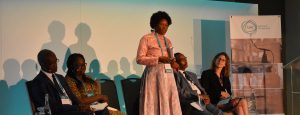 Photo: Angela Tsheole from the Botswana Ministry of Basic Education speaks on the Evidence to Action panel, while co-panellists Raoul Kone, Cynthia Efua Bosumtwi-Sam, Mahuba Hazemba and Habat Abdi, and moderator Laura Poswell listen.