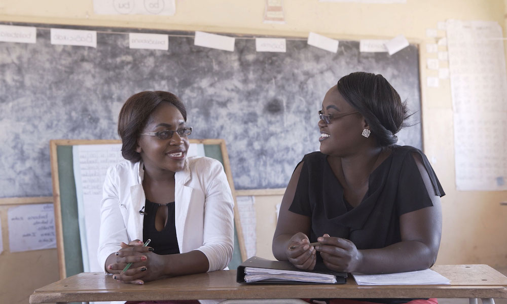 Two women (a mentor and teacher) sit at desk in a classroom, both smiling.
