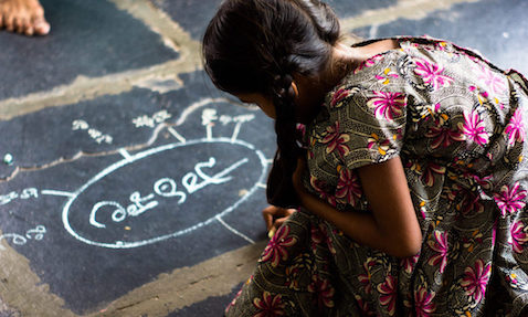 A child in a TaRL class in India writes a mind map on the floor using chalk.