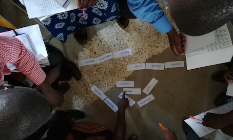 Teachers and mentors rearrange word cards to form sentences, demonstrating a TaRL reading activity during a Catch Up training session in Zambia.