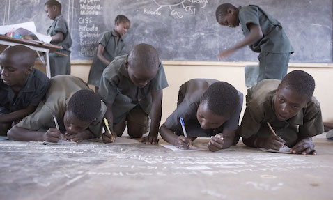 Children write in their notebooks during a reading activity in a Catch Up class in Zambia