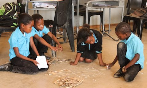 Children in a TaRL class in Botswana solve a maths problem using bundles and sticks.