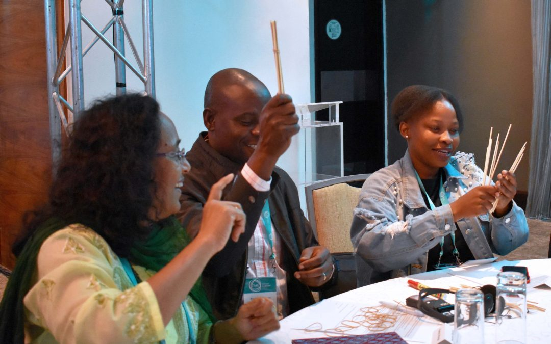 Meera Tendolkar, Fred Abungu, and Moitshepi Matsheng practice a bundle and sticks maths activity at the 2018 TaRL Conference.
