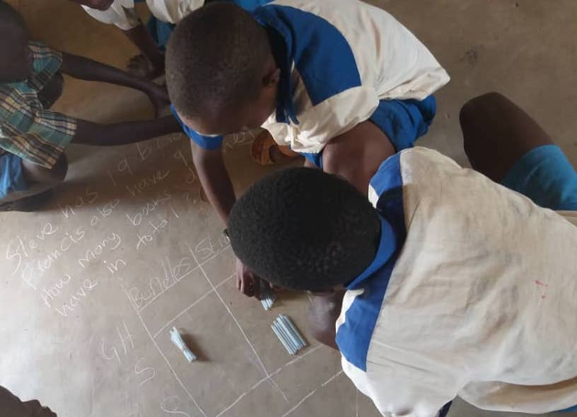 Children in Bungoma use bundles and sticks to solve a maths problem during a TaRL practice session in Bungoma, Kenya.