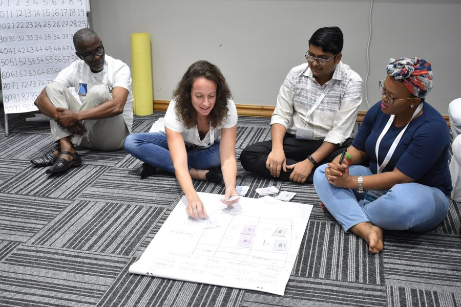 Participants at the TaRL Workshop 2019 practice solving a sum using play money during the TaRL Workshop 2019.