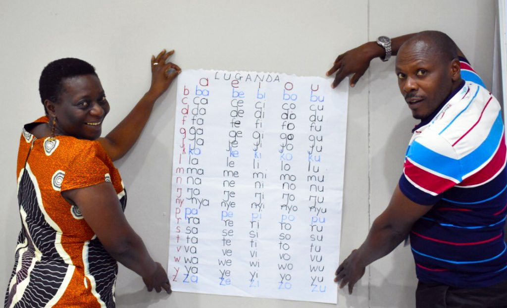 Participants at the 2019 TaRL Workshop show the Luganda phonetic charts they created at the workshop.