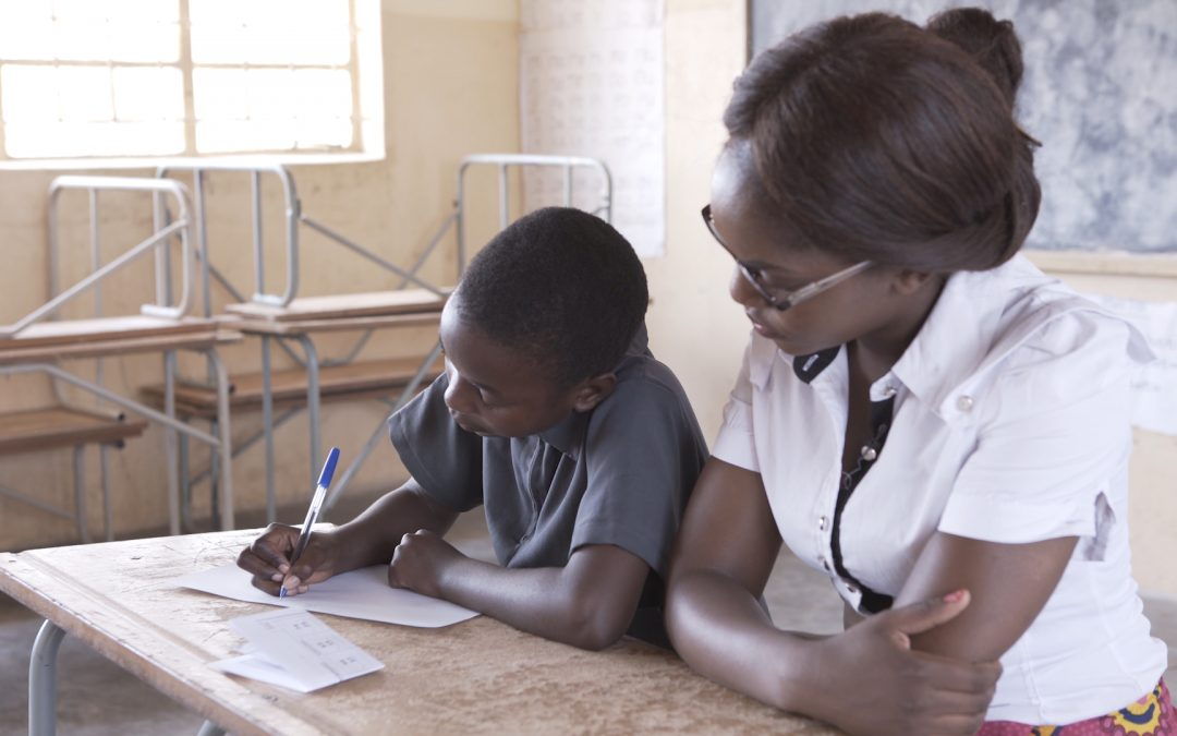 A child completes a sum on a piece of paper while a teacher watches during a TaRL assessment in Zambia.