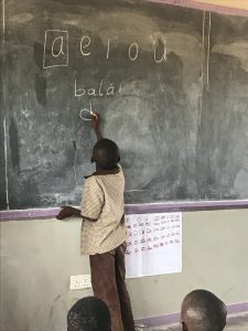 A child writes on the board during a Catch Up class in Kazungula.