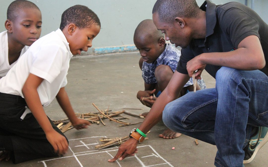 A Young 1ove facilitator points at a sum written in chalk on the floor. Three children look at the sum.