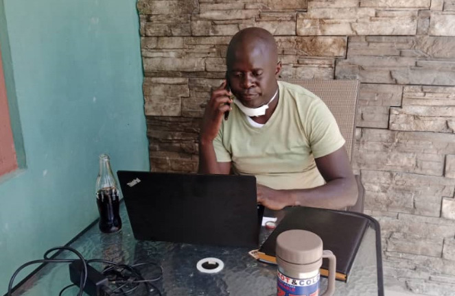 Richard Bwale sits at a table holding a cellphone to his ear, looking at a laptop on the desk in front of him, a medical mask around his neck.