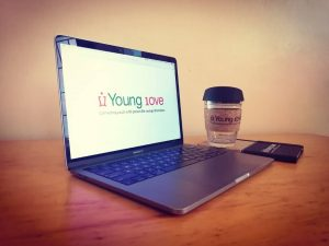 An open laptop with the Young 1ove logo sits on a desk, next to a coffee cup.