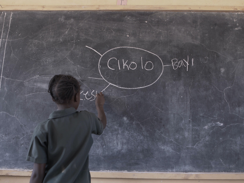 "A child writes the word cesu on a mind map on a board. In the centre of the mind map is the word ""cikolo""."