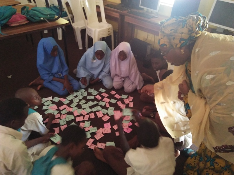 Children in a classroom in Nigeria do a TaRL flash card activity.