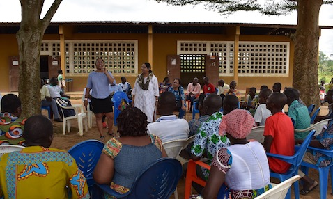 TaRL Africa team members present to community members outside in front of a school in Côte d'Ivoire.